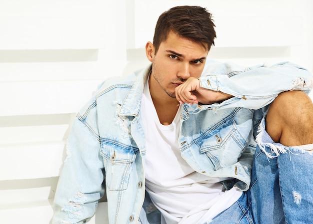 Portret przystojny młody model mężczyzna ubrany w ubrania dżinsy, siedząc w pobliżu białej ścianie teksturowane