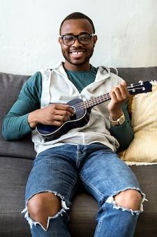 Portret przystojny młody murzyn gra na gitarze w domu.