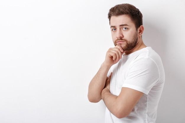 Portret przystojny młody myślący mężczyzna z brodą ooking w kamerę przeciw białej ścianie