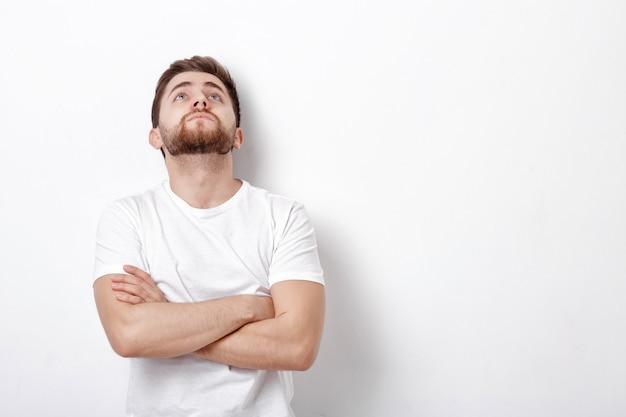 Portret przystojny młody myślący mężczyzna z brodą patrzy przeciw białej ścianie