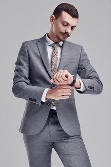 Portret przystojny młody ufny arabski biznesmen z galanteryjnym wąsem w moda kostiumu popielatych pełnych spojrzeniach przy jego zegarkiem na pracownianym tle