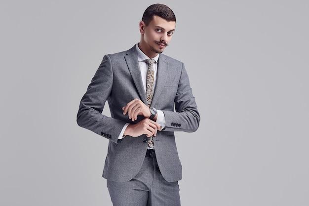 Portret przystojny młody ufny arabski biznesmen z galanteryjnym wąsem w moda szarym pełnym kostiumu przystosowywa jego rękaw na pracownianym tle