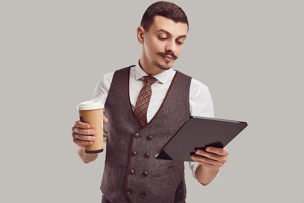 Portret przystojny młody ufny arabski biznesmen z galanteryjnym wąsem w woolen brown kostiumu trzyma pastylkę i filiżankę kawy na pracownianym tle