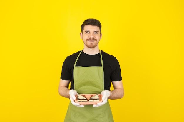 Portret przystojny młodzieniec trzyma kromki ciasta na tacy.