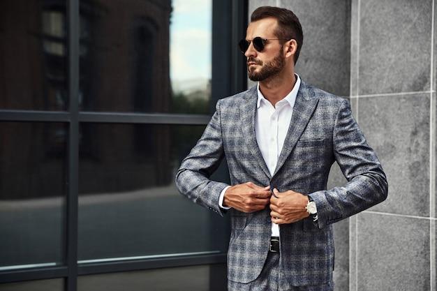 Portret przystojny moda biznesmen model ubrany w elegancki garnitur kratkę