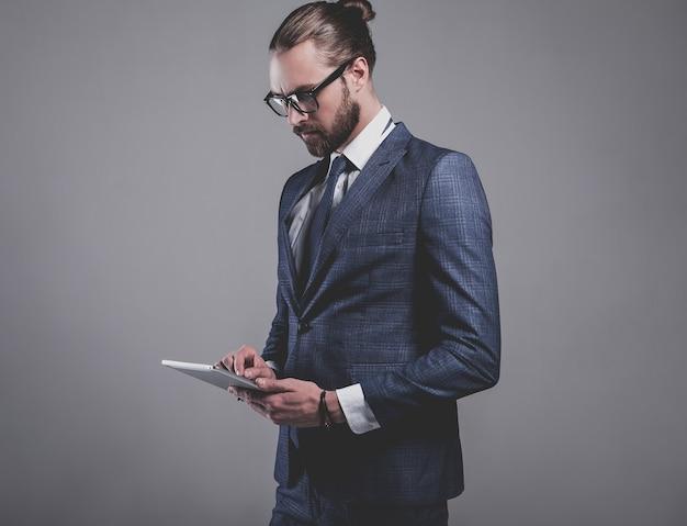 Portret przystojny moda biznesmen model ubrany w elegancki niebieski garnitur w okularach