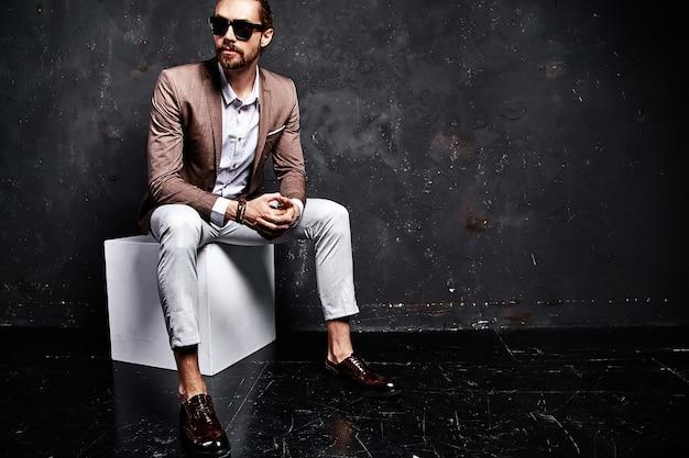 Portret przystojny moda model hipster stylowy biznesmen biznesmen ubrany w elegancki brązowy garnitur siedzi w pobliżu ciemności