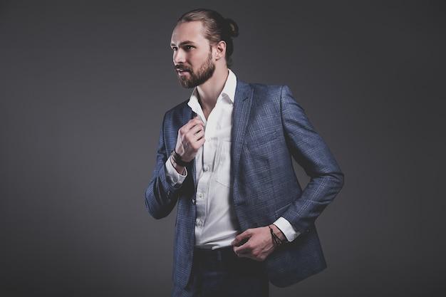 Portret przystojny moda model hipster stylowy biznesmen biznesmen ubrany w elegancki niebieski garnitur pozowanie na szaro