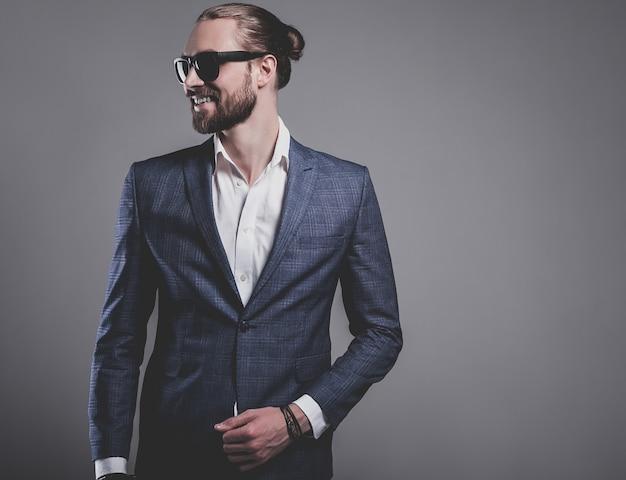 Portret przystojny moda model hipster stylowy biznesmen biznesmen ubrany w elegancki niebieski garnitur w okulary przeciwsłoneczne pozowanie na szaro