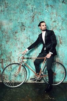Portret przystojny moda stylowy hipster biznesmen model ubrany w elegancki czarny garnitur.