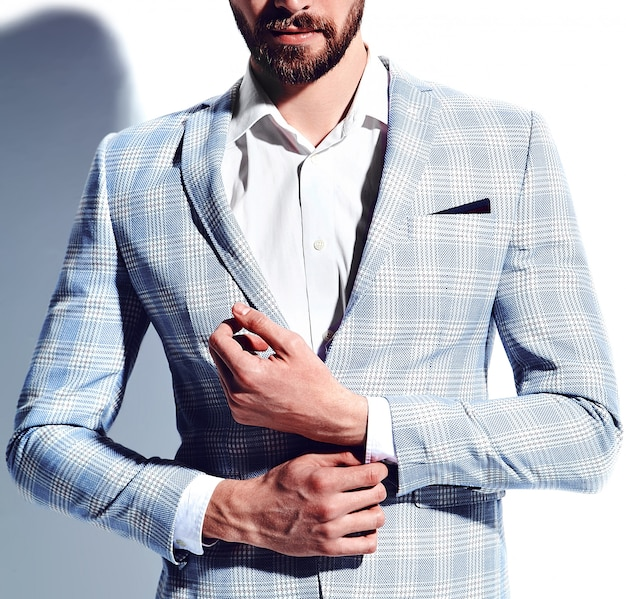 Portret przystojny moda stylowy hipster biznesmen model ubrany w elegancki jasnoniebieski garnitur w okularach na białym tle.