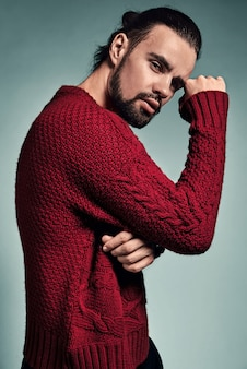 Portret przystojny moda stylowy hipster model ubrany w ciepły czerwony sweter pozowanie studio.