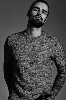 Portret przystojny moda stylowy hipster model ubrany w ciepły sweter pozowanie studio.