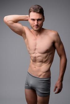 Portret przystojny muskularny mężczyzna bez koszuli na szaro