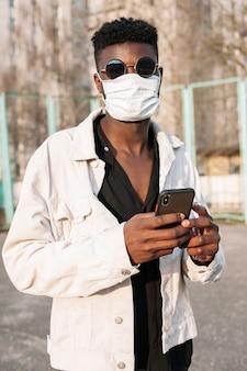 Portret przystojny nastolatek pozuje z medyczną maską