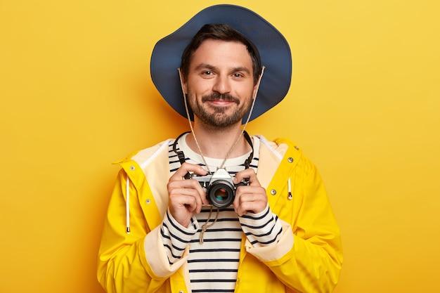 Portret przystojny nieogolony mężczyzna trzyma aparat retro, robi zdjęcia, nosi kapelusz, sweter w paski i płaszcz przeciwdeszczowy, odizolowany na żółtej ścianie