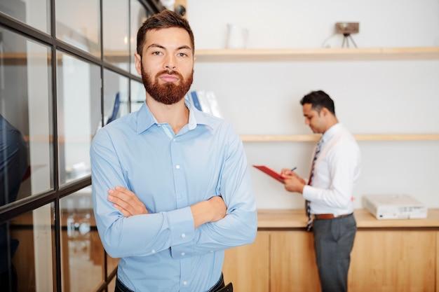 Portret przystojny pewny siebie brodaty przedsiębiorca krzyżujący ramiona i patrzący na kamerę
