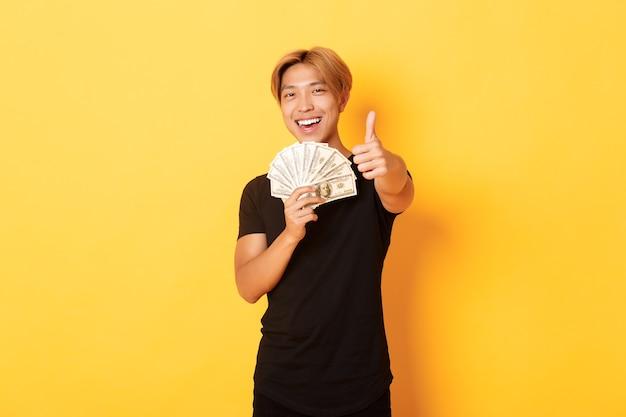 Portret przystojny, pewny siebie uśmiechnięty azjata pokazujący kciuki do góry i trzymający pieniądze, gwarantuje coś, stojąc na żółtej ścianie