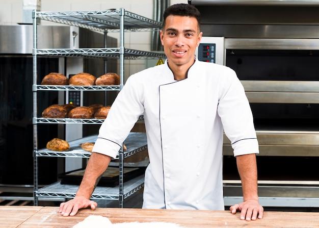 Portret przystojny piekarz przy piekarnią z chlebami i piekarnikiem na tle