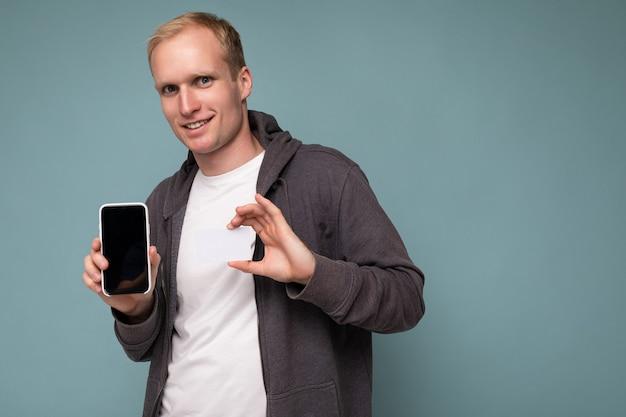 Portret przystojny posiadania smartfona i karty kredytowej