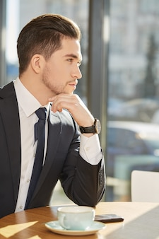 Portret przystojny poważny biznesmen patrzeje daleko od myśleć nad filiżanką kawy przy kawiarnią
