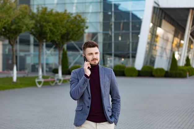 Portret przystojny poważny mężczyzna w przypadkowej odzieży mienia smartphone. menedżer odnoszący sukces wykonuje połączenie. młody biznesmen rozmawia przez telefon, stojąc na ulicy miasta w pobliżu centrum biznesowego