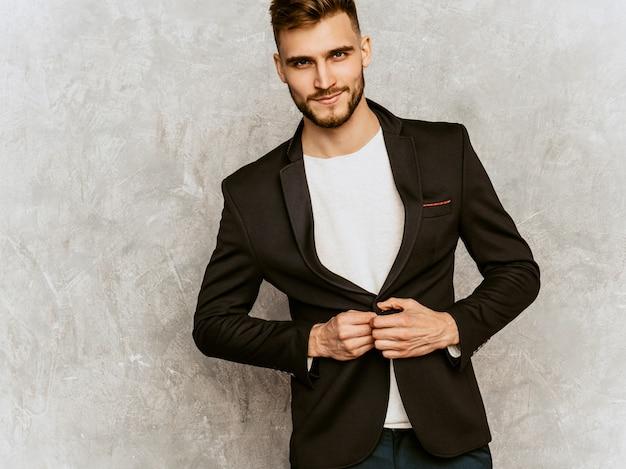 Portret przystojny poważny modnisia biznesmena model jest ubranym przypadkowego czarnego kostium.