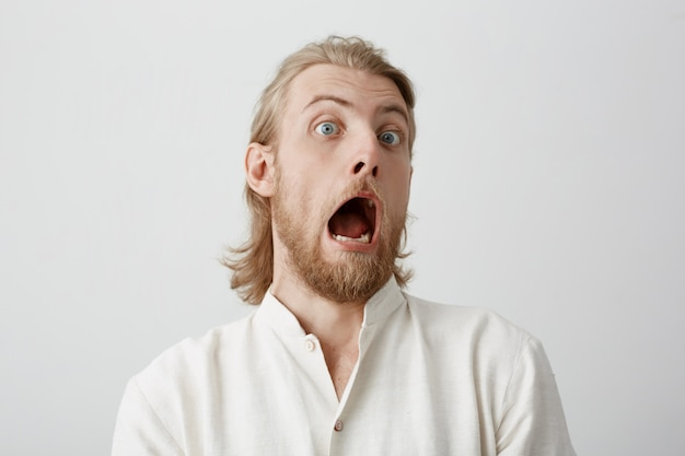 Portret przystojny, przystojny brodaty mężczyzna o jasnych włosach, wyrażający szok lub przerażony czymś