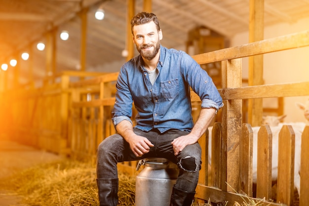 Portret przystojny rolnik siedzi na pojemniku mleka retro w stodole kóz. naturalna koncepcja produkcji i hodowli mleka