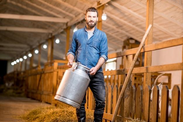 Portret przystojny rolnik stojący z retro pojemnikiem na mleko w stodole kóz. produkcja i hodowla mleka naturalnego