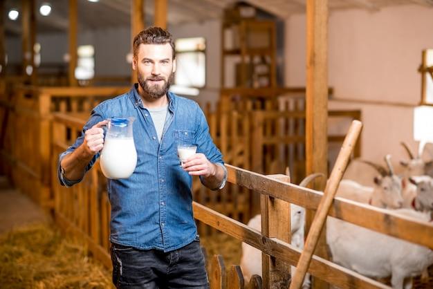 Portret przystojny rolnik ze świeżym mlekiem stojący w stodole kóz z kóz w tle. produkcja i hodowla mleka naturalnego