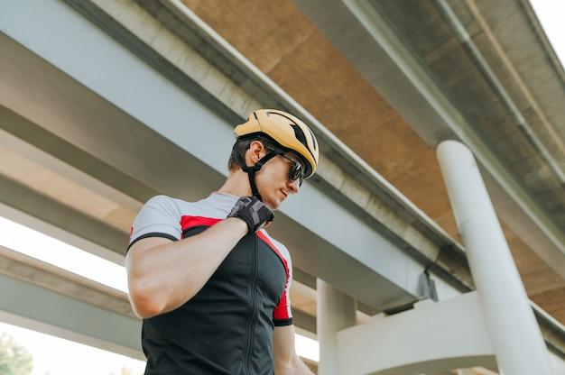 Portret przystojny rowerzysta mężczyzna stojący przed budynkiem