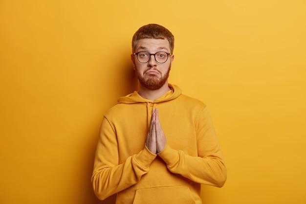 Portret przystojny ściska dłonie, wykonuje gest modlitwy, błaga o pomoc, zaciska usta i patrzy serio, ubrany w luźną bluzę z kapturem, odizolowany na żółtej ścianie. proszę, wyświadcz mi przysługę