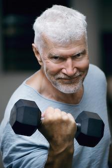 Portret przystojny siwy starszy mężczyzna z hantlami koncepcja sportu i opieki zdrowotnej