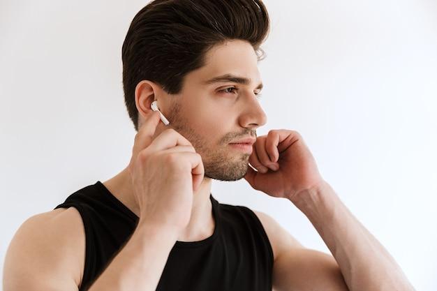 Portret przystojny skoncentrowany młody sportowiec na białym tle nad białą ścianą słuchania muzyki przez słuchawki.