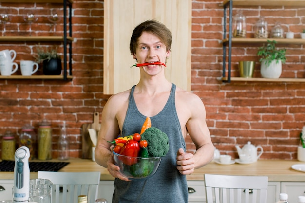 Portret przystojny sportowca trzyma szklaną misę ze świeżymi warzywami i owocami, czerwona papryczka chili w ustach na kuchni w domu
