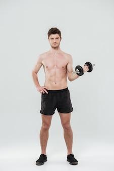 Portret przystojny sprawny sportowiec stojący i trzymając hantle