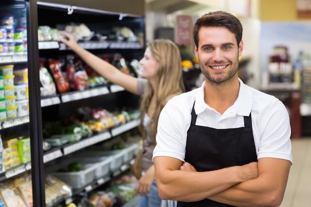 Portret przystojny sprzedawca z ręką skrzyżowaną