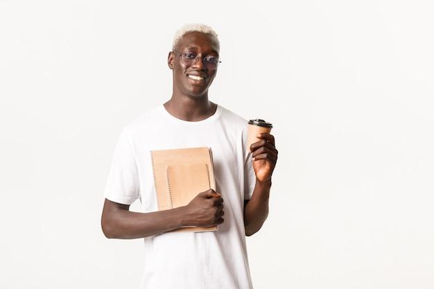 Portret przystojny, stylowy afroamerykanin z blond włosami, idzie do college'u, w okularach, trzymając filiżankę kawy i notebooki
