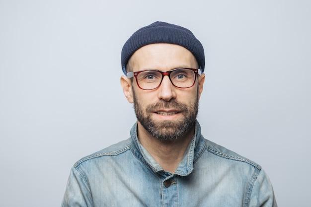 Portret przystojny stylowy dziennikarz mężczyzna nosi okulary, modny kapelusz i dżinsową kurtkę