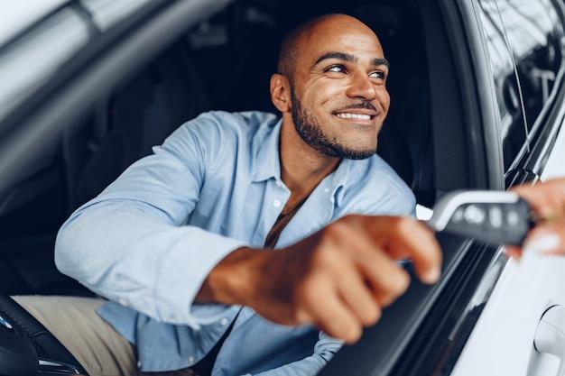 Portret przystojny szczęśliwy african american człowieka siedzącego w swoim nowo zakupionym samochodzie z bliska