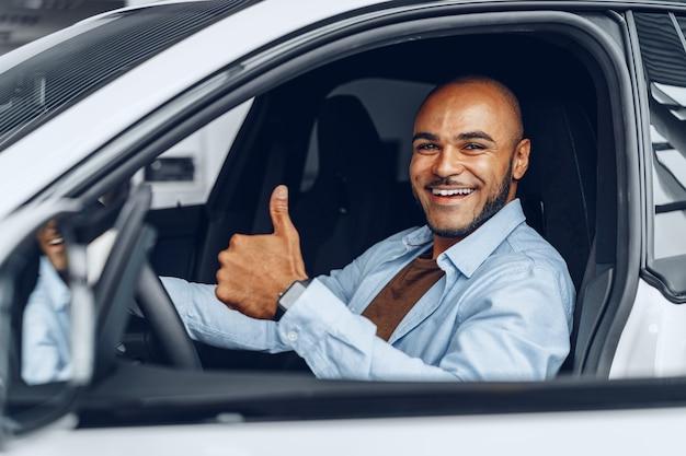 Portret przystojny szczęśliwy african american człowieka siedzącego w swoim nowo zakupionym samochodzie