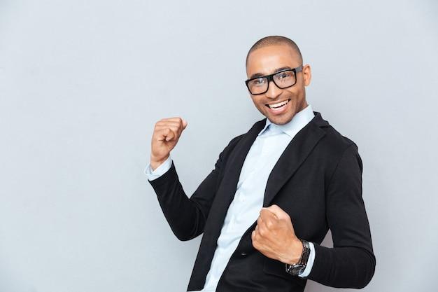 Portret przystojny szczęśliwy afroamerykanin młody człowiek świętuje sukces