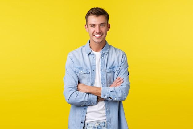Portret przystojny szczęśliwy kaukaski facet z białymi zębami, uśmiechnięty szeroko, skrzyżowane ramiona w klatce piersiowej pewny siebie, stojący żółtym tle w dżinsowej koszuli na białym t-shirt.