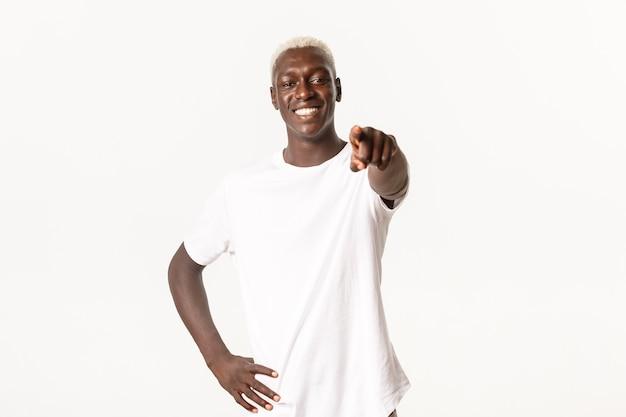 Portret przystojny szczęśliwy mężczyzna afroamerykanin, uśmiechnięty zadowolony i wskazując palcem na aparat