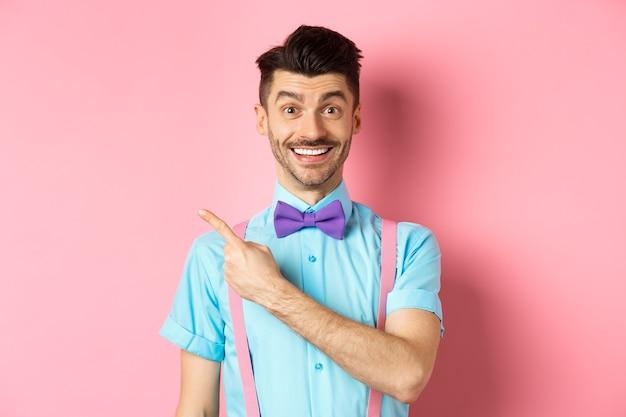 Portret przystojny szczęśliwy mężczyzna pokazujący logo, wskazujący w lewo i uśmiechający się do kamery, polecający ofertę sklepową, stojący na różowym tle.