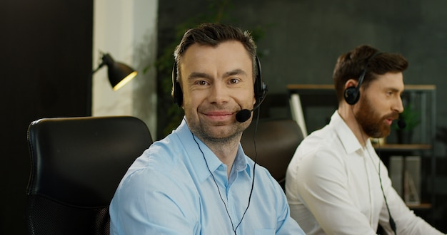 Portret przystojny szczęśliwy mężczyzna w słuchawki pracuje przy komputerem w centrum telefonicznym. mężczyźni operatorzy współpracują ze wsparciem w biurze.