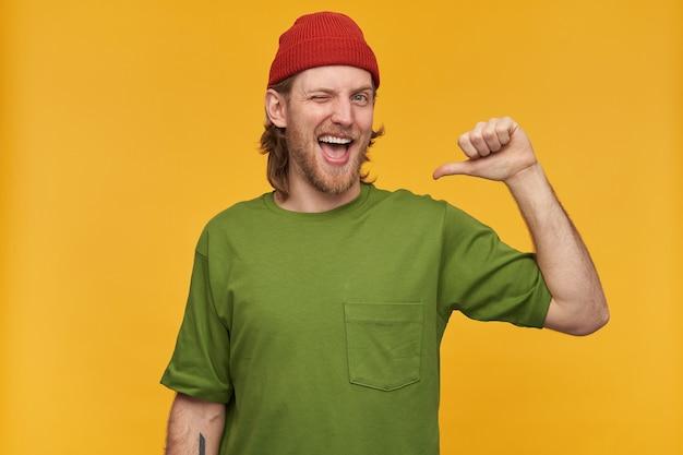 Portret przystojny, szczęśliwy mężczyzna z blond fryzurą i brodą. ubrana w zieloną koszulkę i czerwoną czapkę. ma tatuaż. wskazuje na siebie kciukiem. pojedynczo na żółtej ścianie