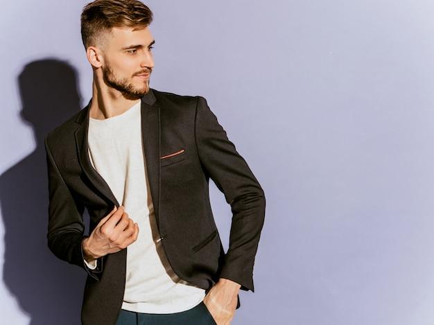 Portret przystojny ufny modnisia biznesmena model jest ubranym przypadkowego czarnego kostium.
