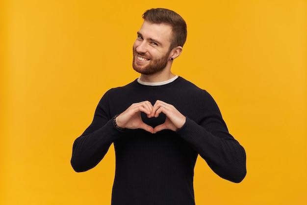 Portret przystojny, uroczy mężczyzna z brunetką i brodą. ma piercing. nosi czarny sweter. pokazuje znak serca i uśmiecha się zalotnie. pojedynczo na żółtej ścianie